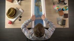 Mannelijke het openen wereldkaart om land voor reisbestemming, vakantie te kiezen
