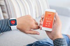 Mannelijke holdingstelefoon en slim horloge met app gezondheidssensor Stock Afbeeldingen