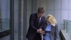 Mannelijke hulp vragende hogere vrouwelijke werkgever om documenten, bedrijfadministratie te ondertekenen stock footage