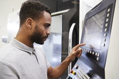 Mannelijke ingenieur die cnc machines in fabriek in werking stellen royalty-vrije stock foto