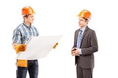 Mannelijke ingenieur die een blauwdruk houden en een gesprek hebben met Royalty-vrije Stock Afbeeldingen