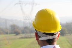 Mannelijke ingenieur die zich bij elektriciteitspost bevinden Stock Foto's