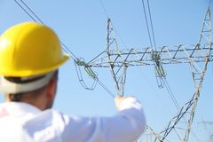 Mannelijke ingenieur die zich bij elektriciteitspost bevinden Stock Foto