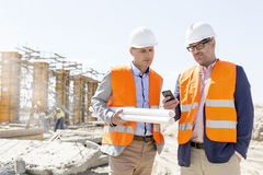 Mannelijke ingenieurs die mobiele telefoon met behulp van bij bouwwerf tegen duidelijke hemel Royalty-vrije Stock Afbeeldingen