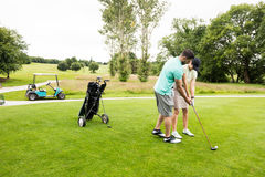Mannelijke instructeurs bijwonende vrouw in het leren van golf royalty-vrije stock afbeeldingen