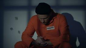 Mannelijke Kaukasische gevangenezitting in cel, gevoel schuldig over misdaden, overtuiging stock video