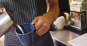 Mannelijke kelners gietende melk in mok bij koffie 4k stock videobeelden