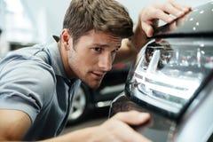Mannelijke klant die en zorgvuldig een nieuwe auto onderzoeken bekijken stock afbeelding