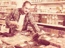 Mannelijke klant die noten en korrel in gemiddelde voedselwinkel kiezen royalty-vrije stock afbeeldingen