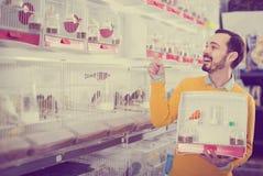 Mannelijke klant die over beste vogel in dierenwinkel beslissen te houden royalty-vrije stock foto