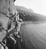 Mannelijke klimmer die grote kei in aard met kabel beklimmen stock fotografie