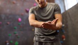 Mannelijke klimmer drogende handen bij binnen het beklimmen gymnastiek stock fotografie
