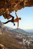 Mannelijke klimmer op overhangende rots stock foto