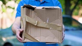 Mannelijke koerier die beschadigde doos, goedkope pakketlevering, slechte verzendingskwaliteit tonen stock foto