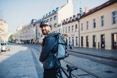 Mannelijke koerier die met rugzak pakketten in stad leveren stock fotografie