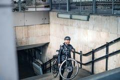Mannelijke koerier die pakketten in stad leveren, die fiets dragen omhoog de treden stock afbeelding