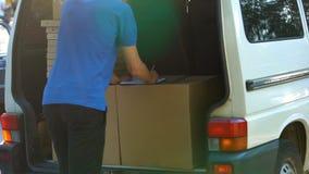 Mannelijke koerier die uitdrukkelijk leveringsdocument op groot vakje in bestelwagen, snelle verzending vullen stock foto's
