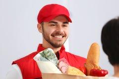 Mannelijke koerier die voedsel leveren aan cliënt stock foto
