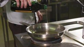 Mannelijke kok die olie in een pan toevoegen stock videobeelden