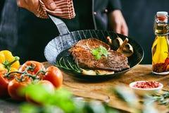 Mannelijke kok die die pan opheffen met vlees wordt gevuld royalty-vrije stock foto's