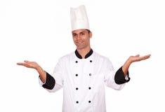 Mannelijke kok die zich met open palmen bevinden Stock Foto's