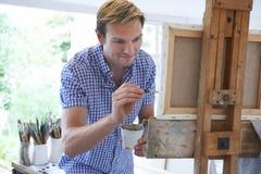 Mannelijke Kunstenaar Painting In Studio stock foto