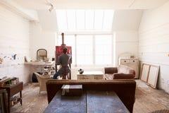 Mannelijke Kunstenaar Working On Painting in Heldere Daglichtstudio stock afbeeldingen
