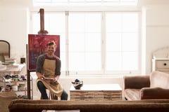 Mannelijke Kunstenaar Working On Painting in Heldere Daglichtstudio royalty-vrije stock afbeeldingen