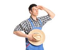 Mannelijke landbouwer die in jumpsuit in de afstand kijken Stock Fotografie