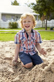 Mannelijke Leerling bij Montessori-School het Spelen in Zand Pit At Breaktime Stock Foto