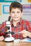Mannelijke Leerling die Microscoop in Wetenschapsles gebruikt royalty-vrije stock afbeelding