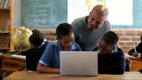 Mannelijke leraar die laptop met student in klaslokaal 4k met behulp van stock video