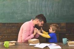 Mannelijke leraar die verklaringen geven aan klein jong geitje De priv?-leraar en zijn kleine student hebben gesprek over gedrag  stock foto