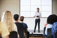 Mannelijke Leraar With Digital Tablet die Presentatie geven aan Middelbare schoolklasse in Front Of Screen stock foto's