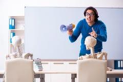 Mannelijke leraar en skeletstudent in het klaslokaal stock fotografie