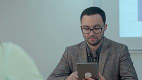 Mannelijke leraar in klassenruimte die de onderworpen gebruikende tablet geven stock video