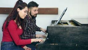 Mannelijke leraar met jonge studente het spelen piano in muzikale school stock footage