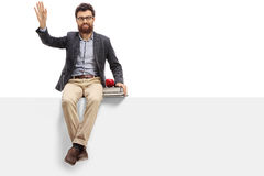 Mannelijke leraarszitting op een paneel en het golven stock afbeelding