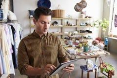 Mannelijke manager die tabletcomputer in klerenwinkel met behulp van stock foto's