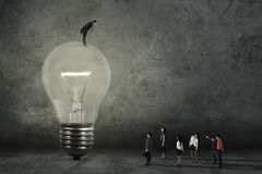 Mannelijke manager met lamp en zijn arbeiders Stock Afbeeldingen