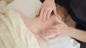 Mannelijke massagetherapeut die gezicht en hoofdmassage doen aan vrouw stock footage