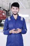 Mannelijke mechanische gebruikscellphone in workshop Royalty-vrije Stock Foto's