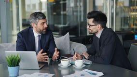 Mannelijke medewerkers die zaken bespreken tijdens middagpauze in moderne koffie stock videobeelden