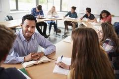 Mannelijke Middelbare schoolprivé-leraar With Pupils Sitting bij de Wiskundeklasse van het Lijstonderwijs stock afbeeldingen