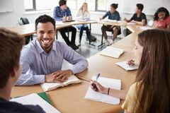 Mannelijke Middelbare schoolprivé-leraar With Pupils Sitting bij de Wiskundeklasse van het Lijstonderwijs royalty-vrije stock afbeelding