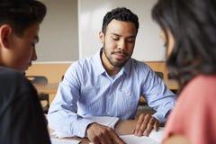 Mannelijke Middelbare schoolprivé-leraar With Two Students bij Bureau in Seminarie stock afbeeldingen