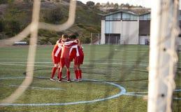 Mannelijke Middelbare schoolvoetballers die Team Talk hebben stock afbeelding