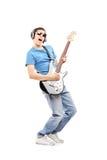 Mannelijke musicus die met hoofdtelefoons een elektrische gitaar spelen Stock Foto