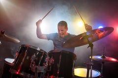 Mannelijke musicus die met trommelstokken trommels spelen Stock Fotografie