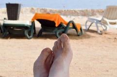 Mannelijke naakte benen, voeten tegen de achtergrond van sunbeds op het strand tegen de achtergrond van een tropische toevlucht Stock Afbeelding